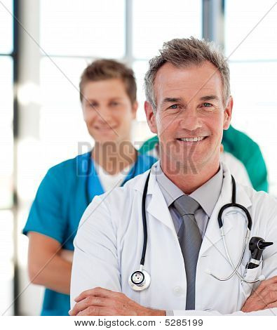 Portrait Of A Mature Doctor Leading His Team