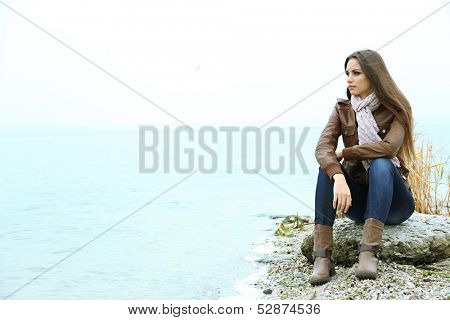 Portrait of young serious woman near river