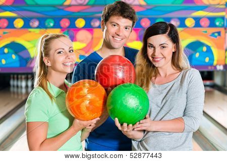 Young people or friends, man and women, playing bowling with a ball in front of the ten pin alley, they are a team