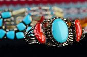 Selective focus on silver bracelet with turquoise and coral gemstones against background of several out of focus Indian artifacts. poster