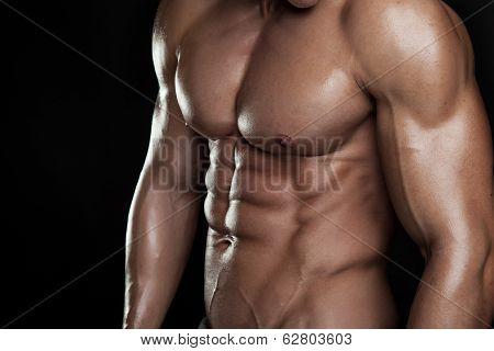 Strong Athletic Man Fitness Model Torso showing six pack abs. isolated on black background poster