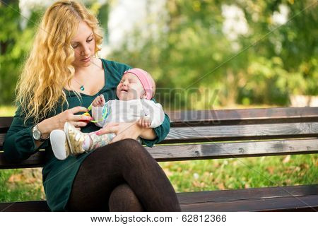 Mom soothes a crying baby, sitting on a park bench