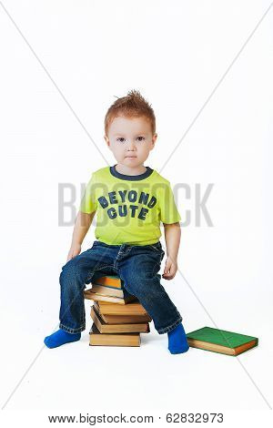 Cute Little Boy Sitting On A Pile Of Books