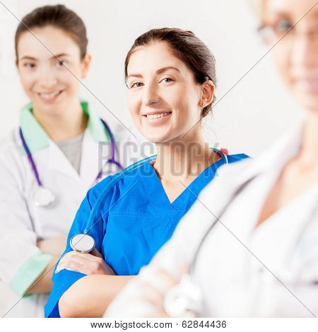 Young smiling nurse in blue with doctors team