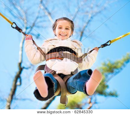 Little girl jumping on the trampoline with rubber bands