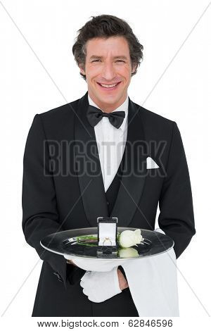 Portrait of happy of server presenting engagement ring and rose isolated over white background