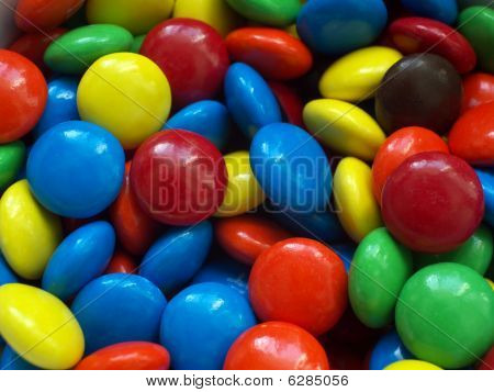 Close up picture of chocolate candy in different colors. poster
