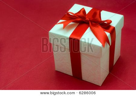 White Gift Box With A Red Ribbon And Bow On Red Background