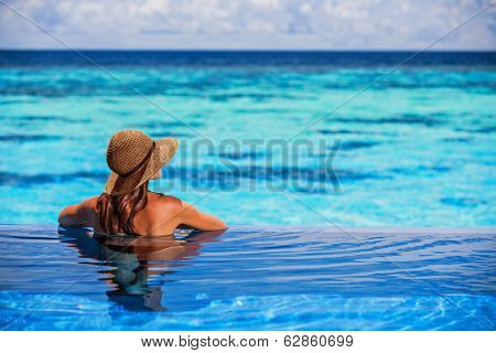 Relaxing on beach resort, back side of sexy woman enjoying seascape from endless pool, luxury summer vacation, travel and tourism concept poster