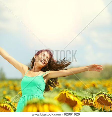 Happy woman in sunflower field. Summer girl in flower field cheerful and joyful. Multiracial Asian Caucasian young woman dancing, smiling elated and serene with arms raised up. poster