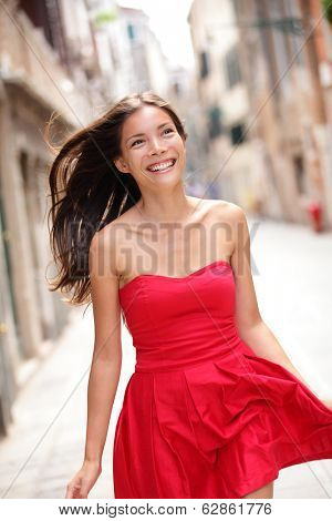 Asian beautiful woman in summer dress walking and running joyful and cheerful smiling in street. Pretty sexy fashion model girl in her 20s. Mixed race Asian Caucasian female model outside.
