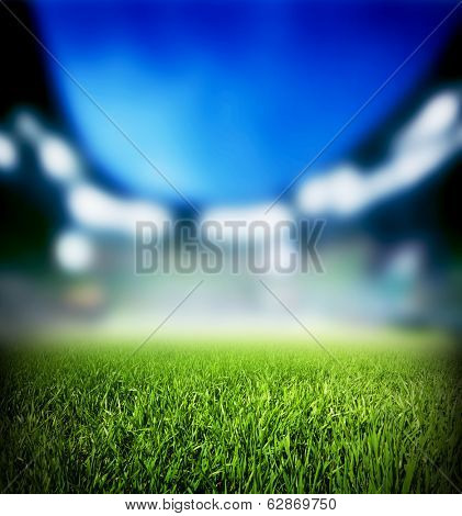 Football, soccer match. Grass close up. Night event lights on the stadium.