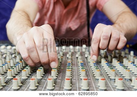 close-up hands of sound engineer work with faders and knobs on professional audio musical mixer