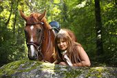 Beautiful girl and brown horse portrait in mysterious forest in summer poster