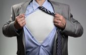 Businessman in classic superman pose tearing his shirt open to reveal t shirt with blank chest for message poster