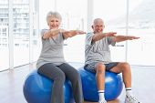 Happy senior couple doing stretching exercises on fitness balls in the medical office poster