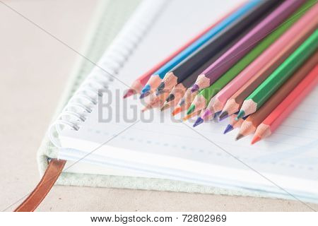 Closeup Colorful Pencil Crayons On Spiral Notebook And Green Notebook