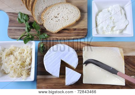 Healthy Food Diet: Probiotic Food including sour dough bread sauerkraut yogurt Parmigiano-Reggiano and Camembert cheeses on wood chopping boards against a blue background. poster