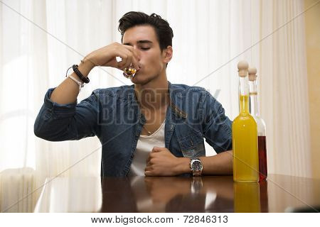 Young Man Sitting Drinking Alone At A Table With Two Bottles Of Liquor