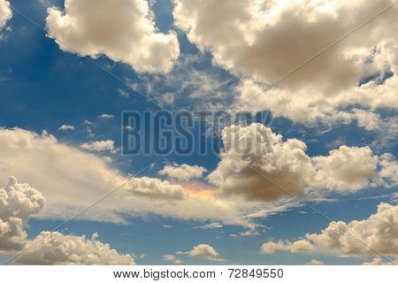 High clouds in a bright blue sky features a sundog rainbow