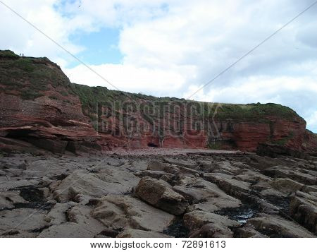 Red standstone rock formation on the coast near Arbroath in Scotland poster