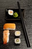 Mix of sushi with chopstick and bowl with wasabi sauce poster