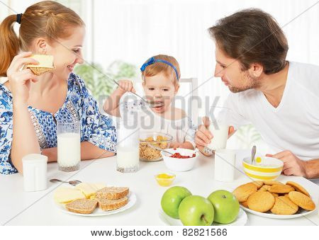 Happy family mother father child baby daughter having breakfast at home poster