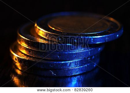 Heap of coins on wooden table, macro view