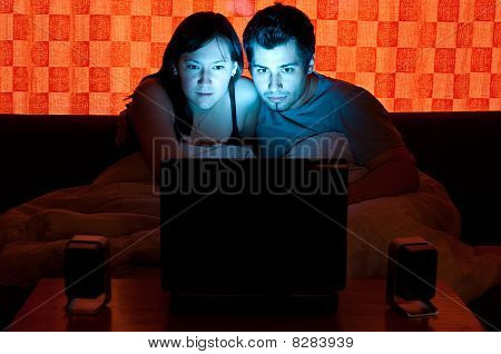Couple On A Couch Watching A Movie On A Laptop