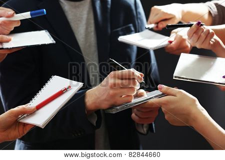 Elegant man signing autograph in notebook on dark background