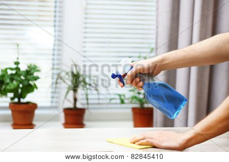 Male hands with sprayer and rag wash windowsill on window background