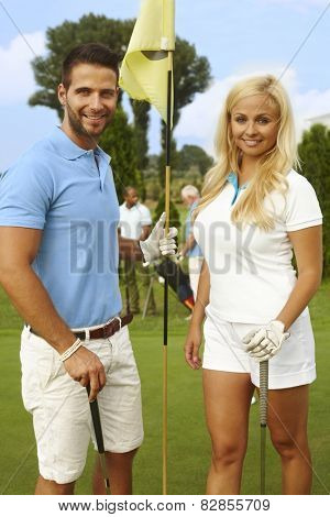 Attractive, young golfers standing on the green, smiling, looking at camera.