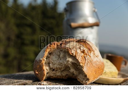 Rustically Bread And Milk Churn On A Wooden Table