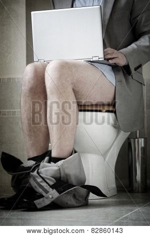 Businessman working on laptop while sitting on toilet concepts for urgent deadline, working from home, workaholic and internet addiction