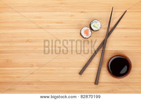 Maki sushi, chopsticks and soy sauce on bamboo wooden table background with copy space