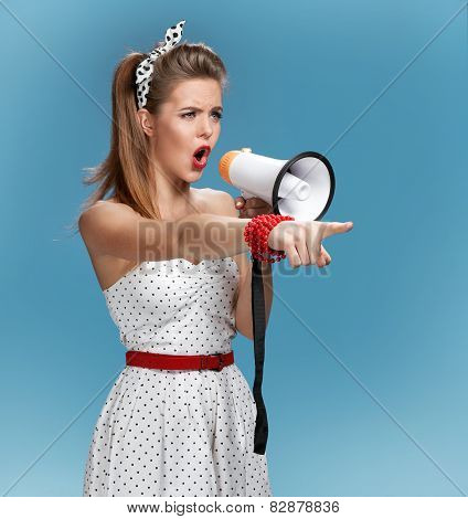 Formidable pin-up girl shouting into a megaphone, mouthpiece, speaking trumpet