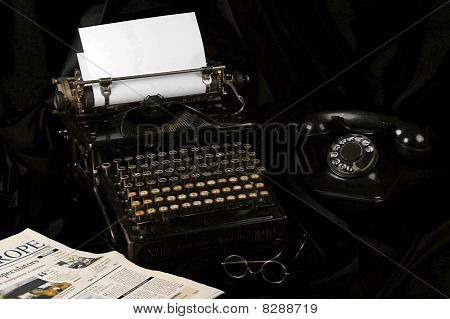 Old fashioned vintage photo of an old type writer with phone glasses and newspaper poster