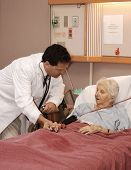 doctor visiting senior woman patient in hospice poster