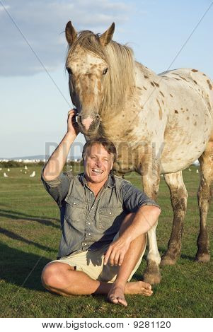 happy smiling man petting an appaloosa horse