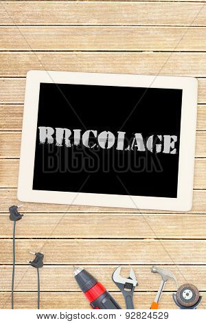 The word bricolage against tools and tablet on wooden background