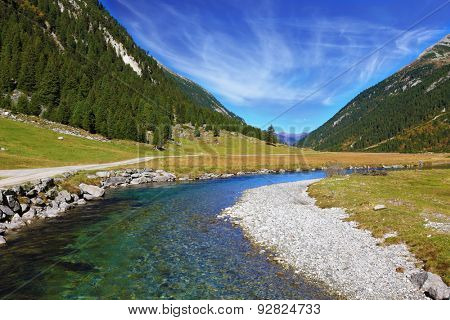 Austrian Alps. Headwaters of the famous Krimml waterfalls. The crystal clear transparent water glows in the midday sun