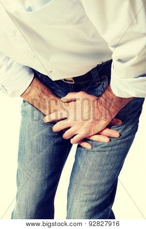 Close up on a man covering his painful crotch. poster