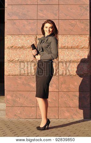 Pretty Woman Portrait Near Wall With Notebook