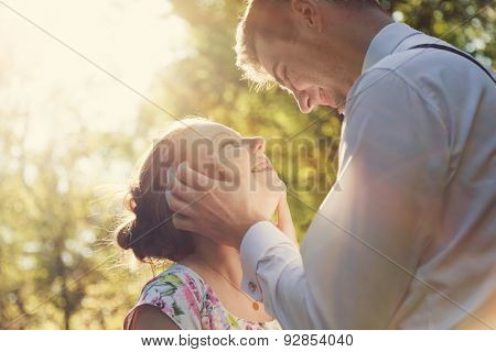 Young romantic couple flirting in sunshine. Dating, love, romance, vintage flare.