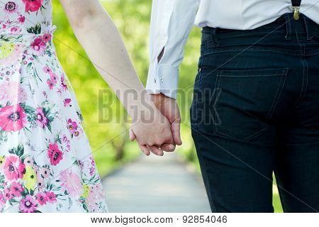 Young couple in love holding hands in summer park. Woman in dress and man wearing elegant shirt. View from the back. Date, fiance with fiancee, hand in hand concepts