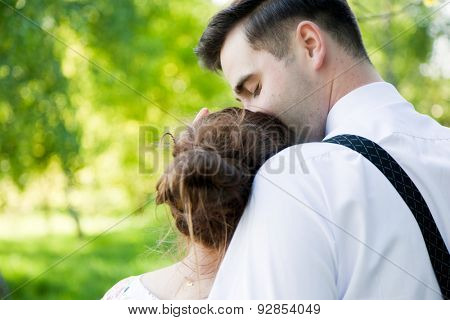 Young handsome man embracing and gently kissing his fiancee in summer green park.  View from the back. Date, fiance with fiancee, couple in love.