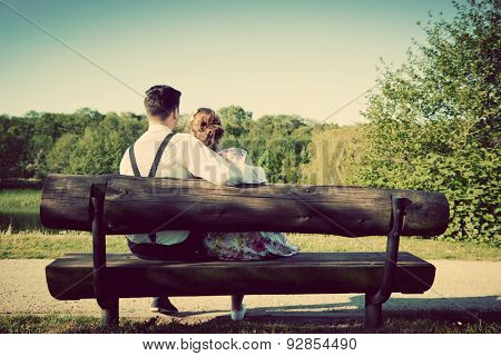 Young couple in love sitting together on a bench in summer park. Man wearing shirt with suspenders. Happy future, marriage concepts. Vintage poster