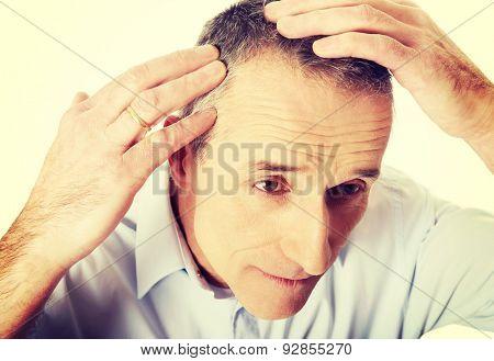 Above view of a man examining his hair.