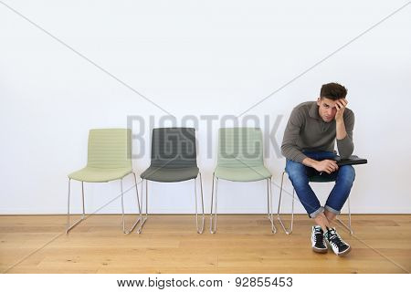 Young man in waiting room for job interview poster