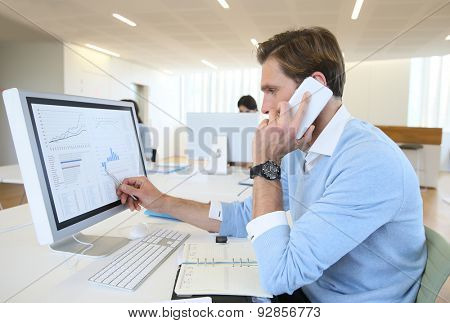 Bank trader negotiating on the phone from office